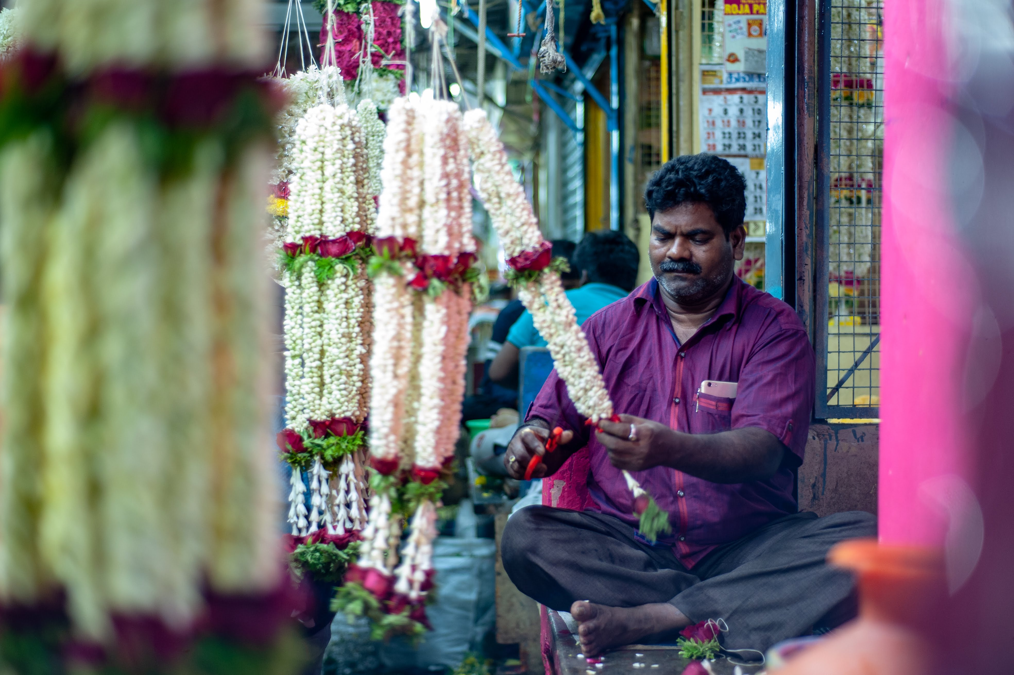 A flower vendor, sitting cross legged, works away on his orders for the day.