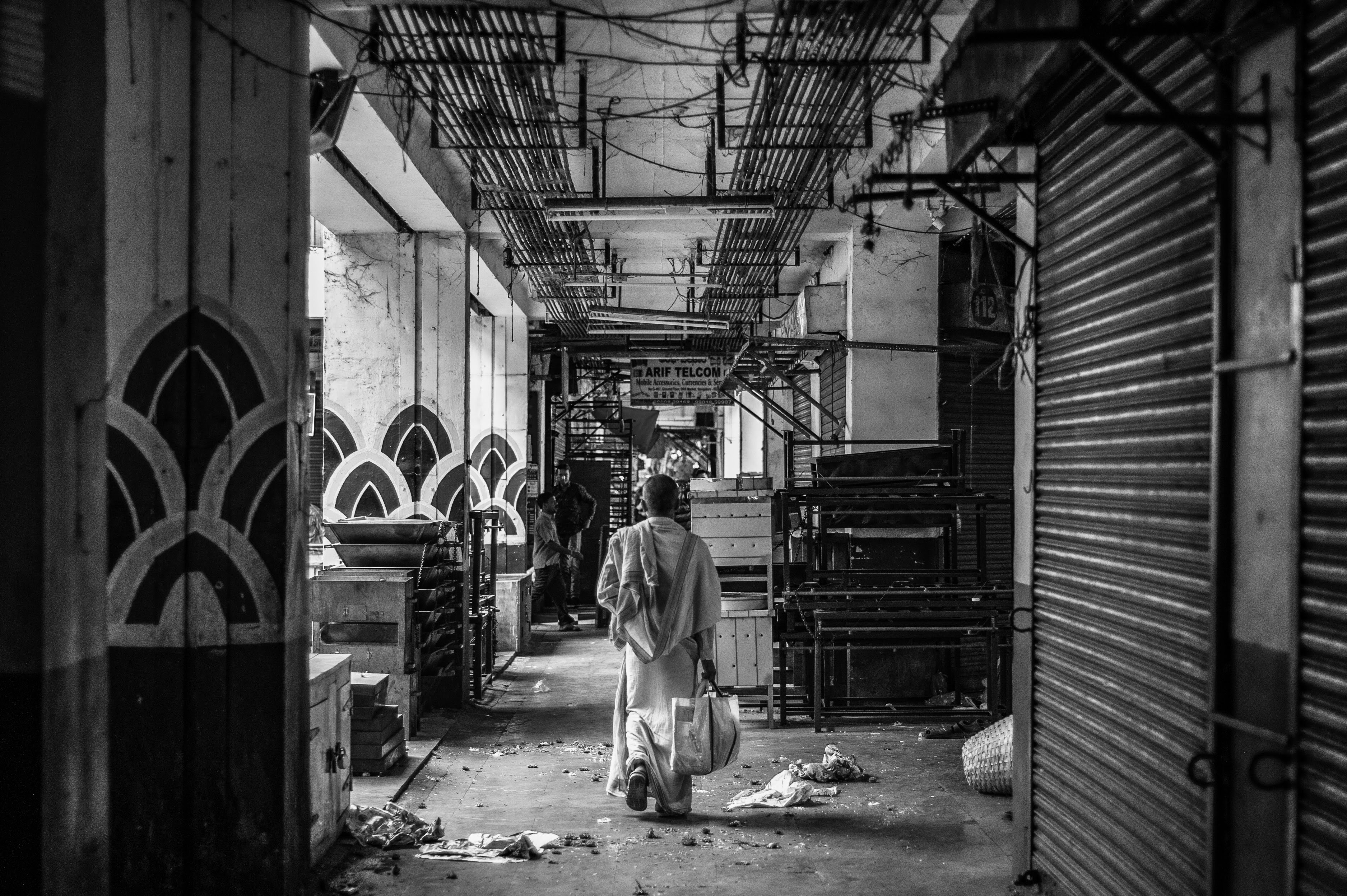A black and white image of man carrying a plastic bag, walking through an empty KR Market in Bangalore.