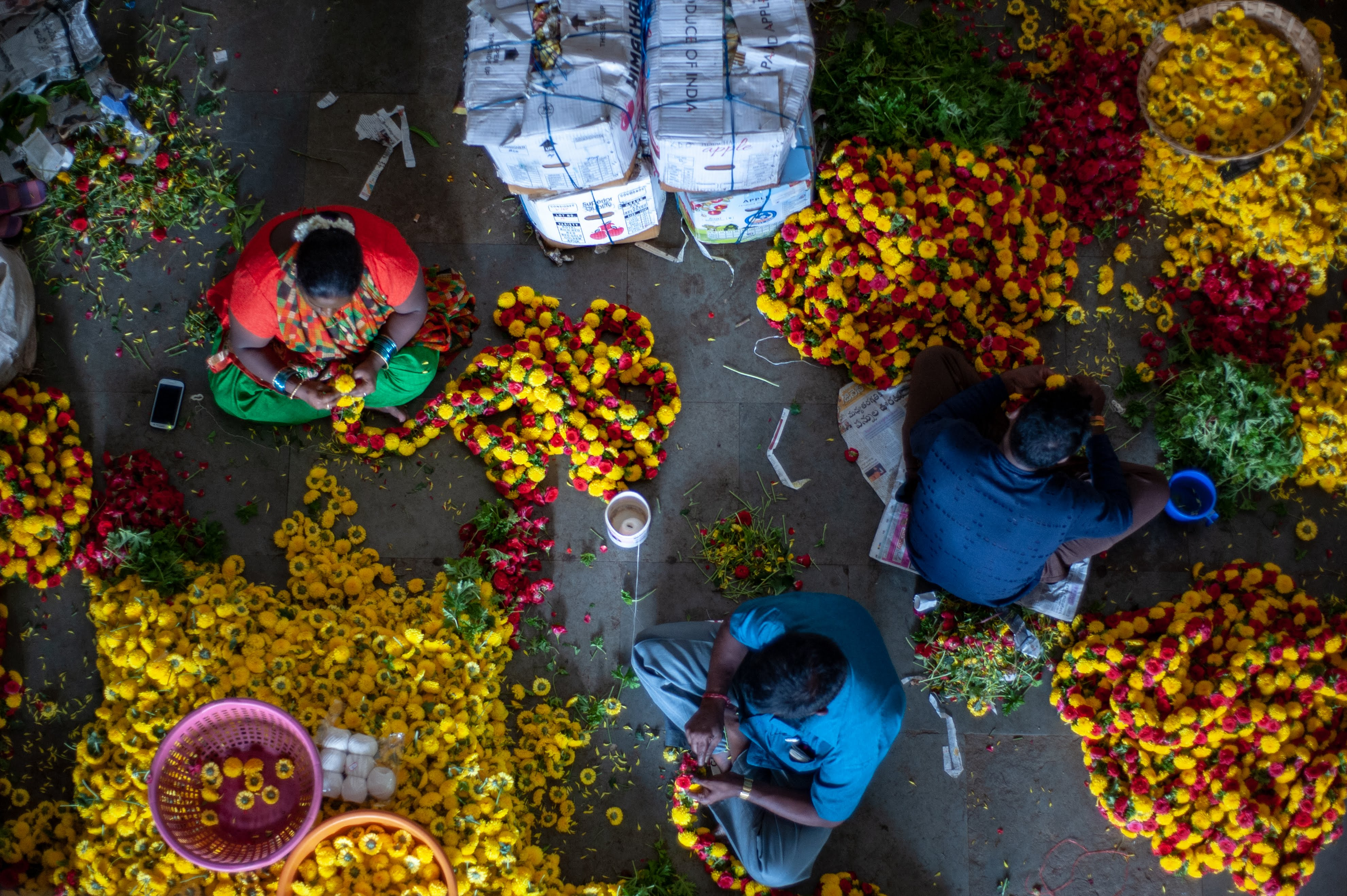 A top shot of three people who are working with individual marigold flowers to create garlands at Bangalore's KR Market.