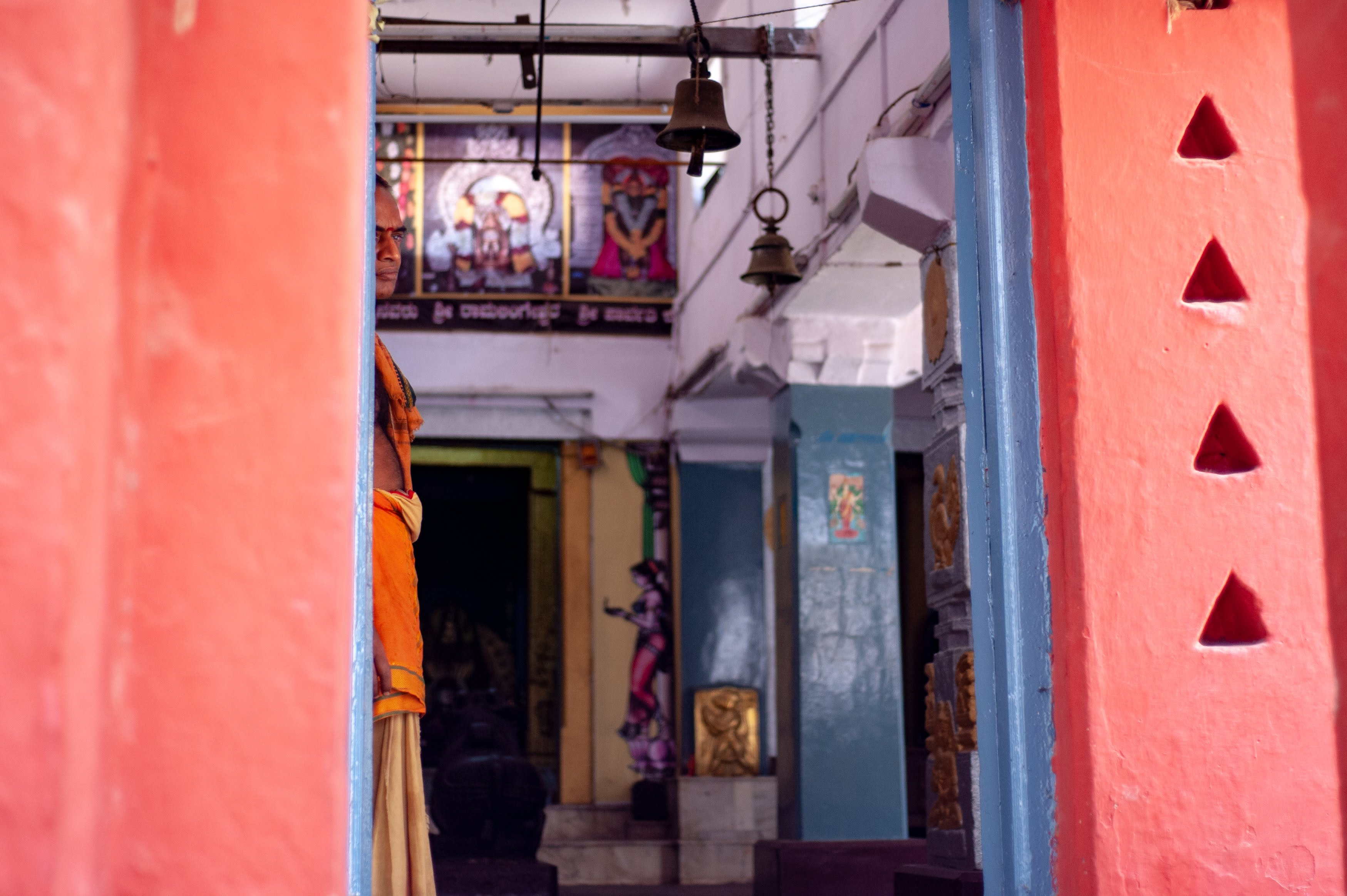 The temple priest of Chowdeshwari Temple in Chikpet, Bangalore watches the street through the temple's doorway.