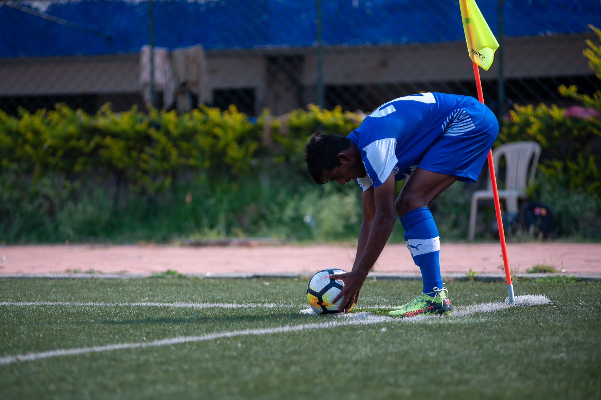 The left winger of Bengaluru FC B bends low to place the ball at the corner flag to take a corner.
