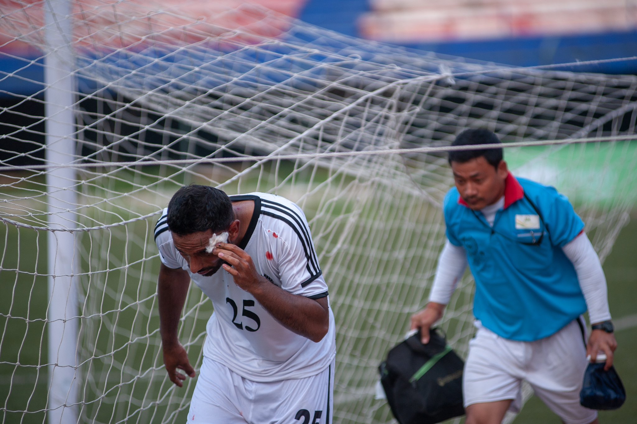 A Mohammedan Sporting player comes off briefly due to a head injury. He is seen here navigating his way to the bench from behind his goal.