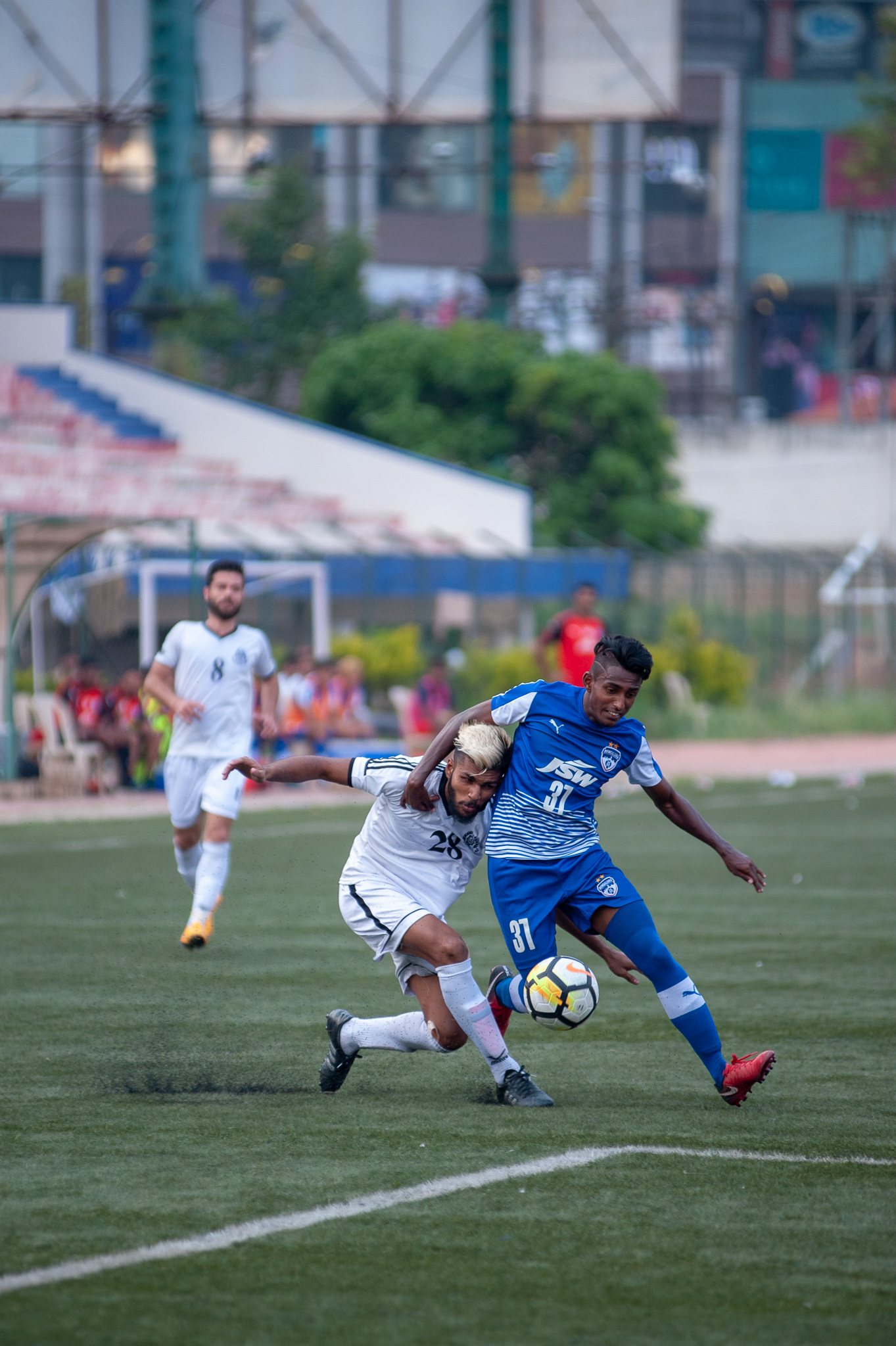 Leon Augustine tussles with a Sporting Mohammedan player for the ball on the right wing before firing in a cross.