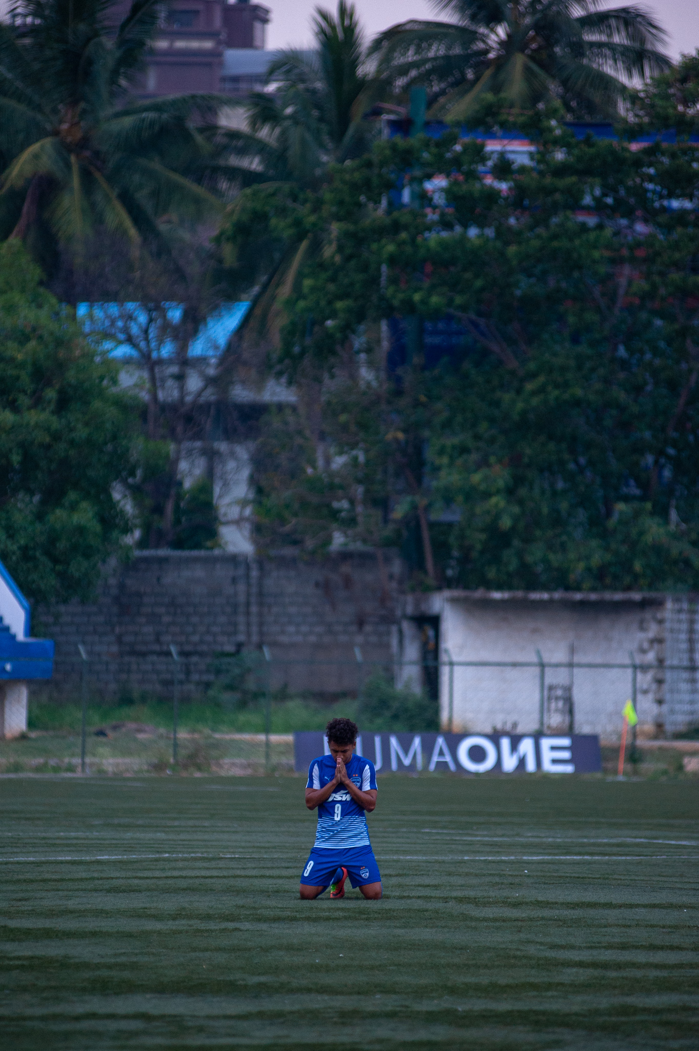 A Bengaluru FC B player is on his knees, hands folded in prayer, after the referee blows the final whistle. The Blues won the game 2 goals to one.