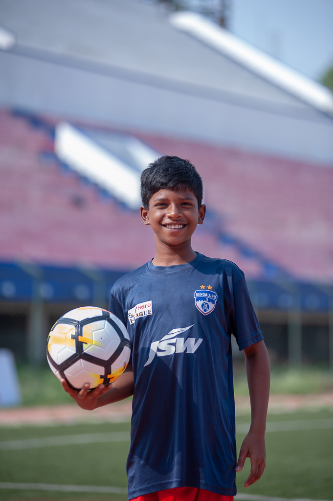 Portrait of a ball boy, named Joshua, holding a ball, looking into the camera and smiling.