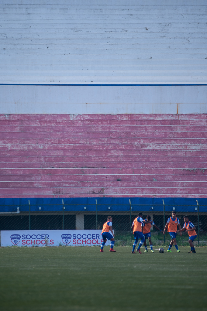 BFC B's substitutes warm up before an advertising board for Bengaluru FC's Soccer Schools.
