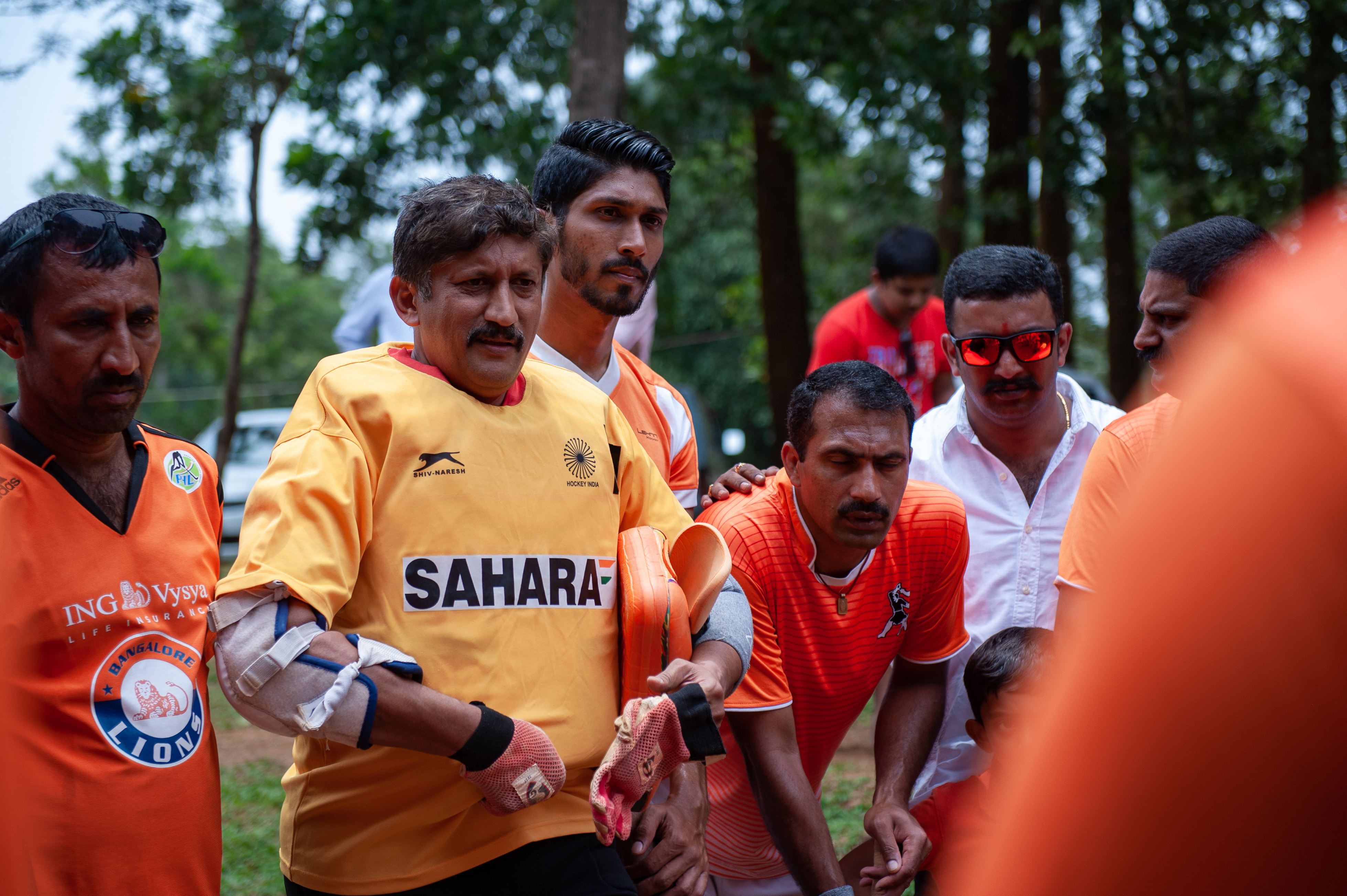 Dr. A B Subbaiah, goalkeeper of the Anjaparvanda, dressed in an India jersey, is seen giving a pep talk to his teammates before the start of the game.
